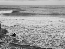 有一个风帆冲浪委员会的人以波浪为背景和海起泡沫 库存照片