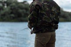 有一个饲养者的渔夫在河前面 免版税库存图片