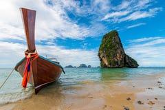 有一个马达的一条木泰国小船在一高clif的背景 免版税库存照片