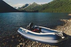 有一个马达的可膨胀的小船在一个美丽的美丽如画的湖 免版税图库摄影