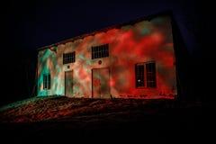 有一个鬼魂的老房子在森林里在晚上或雾的被放弃的被困扰的恐怖议院 老神秘的大厦在死的树森林C里 库存照片