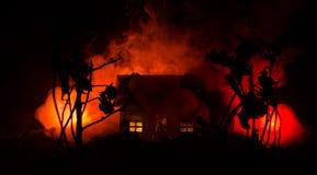 有一个鬼魂的老房子在被月光照亮夜或雾的被放弃的被困扰的恐怖议院 与超现实的大满月的老神秘的别墅 库存图片