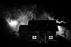 有一个鬼魂的老房子在被月光照亮夜或雾的被放弃的被困扰的恐怖议院 与超现实的大满月的老神秘的别墅 图库摄影
