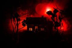 有一个鬼魂的老房子在被月光照亮夜或雾的被放弃的被困扰的恐怖议院 与超现实的大满月的老神秘的别墅 库存照片