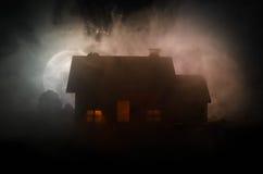 有一个鬼魂的老房子在被月光照亮夜或雾的,与超现实的大满月的老神秘的别墅被放弃的被困扰的恐怖议院 免版税库存照片