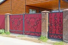 有一个黑伪造的样式的红色金属门在柏油路附近的街道上 免版税库存图片