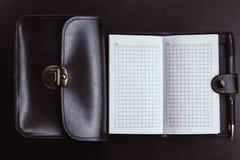 有一个黑袋子的空的笔记本 库存照片