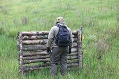有一个轴和一个背包的男性旅客在绿色山和木柴背景  免版税库存照片