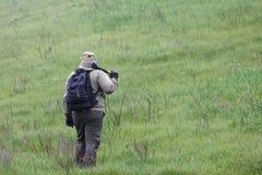 有一个轴和一个背包的男性旅客在绿色山和木柴背景  免版税库存图片