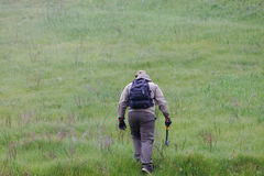 有一个轴和一个背包的男性旅客在绿色山和木柴背景  免版税图库摄影