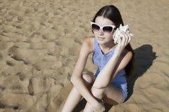 有一个贝壳的美丽的女孩在海滩 免版税图库摄影