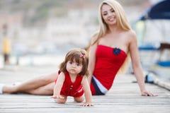 有一个年轻女儿的愉快的母亲在游艇俱乐部附近 库存图片
