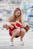 有一个年轻女儿的愉快的母亲在游艇俱乐部附近 免版税库存照片