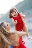 有一个年轻女儿的愉快的母亲在游艇俱乐部附近 免版税库存图片