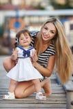 有一个年轻女儿的愉快的年轻母亲在游艇俱乐部附近 免版税图库摄影