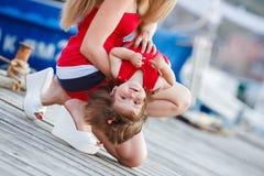 有一个年轻女儿的愉快的年轻母亲在游艇俱乐部附近 免版税库存照片