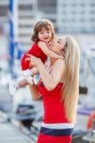 有一个年轻女儿的愉快的年轻母亲在游艇俱乐部附近 图库摄影
