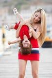 有一个年轻女儿的愉快的年轻母亲在游艇俱乐部附近 免版税库存图片