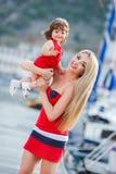 有一个年轻女儿的愉快的年轻母亲在游艇俱乐部附近 库存图片