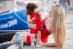 有一个年轻女儿的年轻母亲在游艇俱乐部附近 库存照片