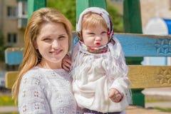 有一个婴孩的一个年轻母亲她的胳膊的 库存照片