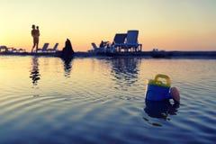 有一个婴孩的一名妇女在日落的海滩的 库存图片