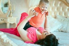 有一个婴孩的妇女在床上 免版税库存图片
