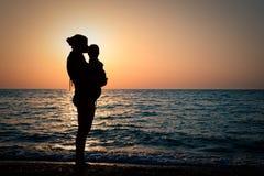 有一个婴孩的妇女在日落的手上 免版税库存图片