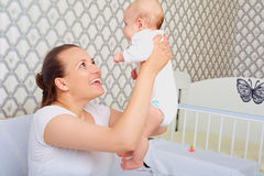 有一个婴孩的愉快的母亲她的胳膊的 E 小妈妈 库存图片