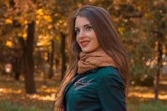 有一个围巾和黑暗的夹克立场的美丽的女孩在公园看起来去微笑 免版税库存图片