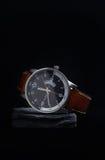 有一个黑拨号盘的手表在一块灰色石头 库存照片