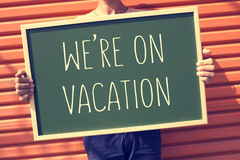 有一个黑板的年轻人有文本的我们是在度假, fi 免版税库存图片