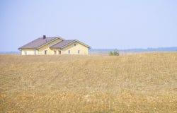 有一个黄色房子的农田 库存图片