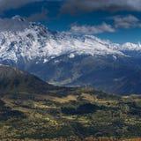 有一个绿色领域倾斜、树木繁茂的山和被雪包围住的峰顶的山全景在背景中 Svaneti,佐治亚 库存图片