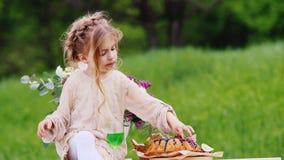 有一件巧妙的轻的礼服的愉快的女孩有一种被弄乱的发型的坐一张装饰的桌并且吃巧克力杯形蛋糕 股票视频