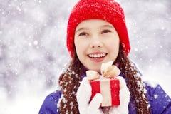 有一件礼物的十几岁的女孩在他们的手上 库存图片
