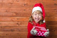 有一件礼物的愉快的孩子在与拷贝空间的木背景 图库摄影