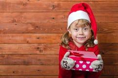 有一件礼物的愉快的孩子在与拷贝空间的木背景 库存照片