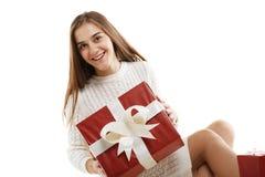 有一件红色礼物和一条白色丝带的女孩,隔绝在白色背景 库存图片