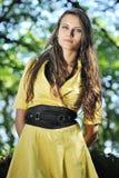 有一件黄色礼服的一个女孩。 库存图片