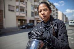 有一件黑盔甲的妇女在摩托车 图库摄影