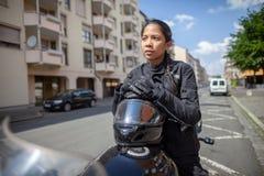 有一件黑盔甲的妇女在摩托车 库存照片