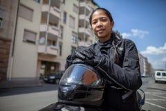 有一件黑盔甲的妇女在摩托车 免版税库存图片