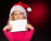 有一份信函的女孩给圣诞老人 免版税图库摄影