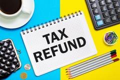 有一份退还税金的笔记笔记本与在黄色蓝色背景的办公室工具 概念退还税金 免版税库存图片