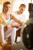 有一位个人教练员的监督的健身房妇女 免版税库存图片