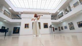 有一位女性小提琴手的画廊大厅一件白色礼服的 股票视频