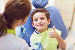 有一位牙医的一个孩子在一个牙齿办公室 免版税库存照片