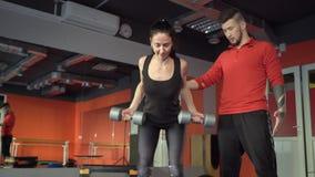 有一位英俊的有用的个人教练员的年轻健康运动的活跃形状女孩在她旁边在健身房 影视素材
