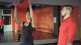 有一位英俊的有用的个人教练员的年轻健康运动的活跃形状女孩在她旁边在健身房 股票录像